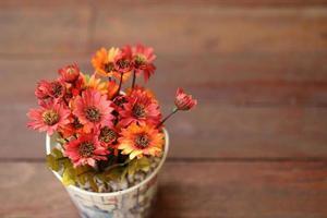 künstliche Blumen in kleinem Topf auf Holztisch.
