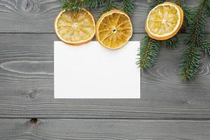 Fichtenzweig mit getrockneten Orangenscheiben und Grußkarte