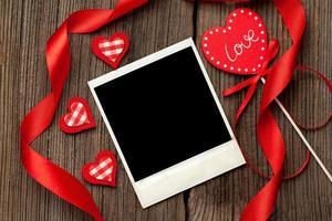 leerer Polaroid-Fotorahmen mit Herzen und Bändern zum Valentinstag foto