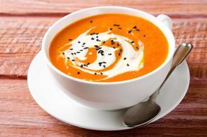 Kürbissuppe mit Tomaten, Chili, Joghurt und schwarzem Sesam foto
