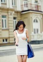 lächelnde junge Frau einkaufen foto