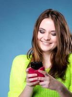 glückliches Mädchen mit Handy liest Nachricht foto