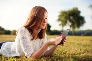 schöne junge Frau mit digitaler Tablette im Park