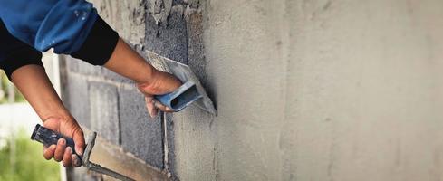Betonputzer, der an einem Haus arbeitet foto