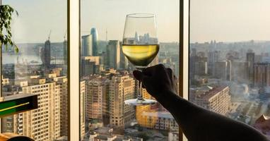 Frau hält Weißweinglas
