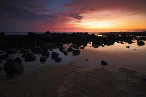 felsige Küste des Sonnenuntergangshimmels