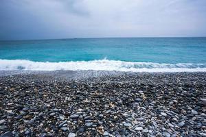 Steinstrand, Meer und Himmel foto