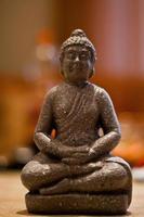 Buddha-Miniaturstatue mit Bokeh-Hintergrund.