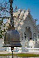 Glocke mit Wat Rong Khun, Thailand im Hintergrund foto
