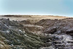 Küste mit Steinen des Vulkanflusses