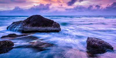 Wellen und Felsen am Strand des Sonnenuntergangs