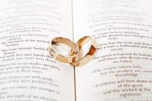 zwei Eheringe an einer Bibel, Korinther Kapitel 13 foto
