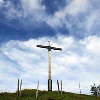 Kreuz vor blauem Himmel mit Wolken foto