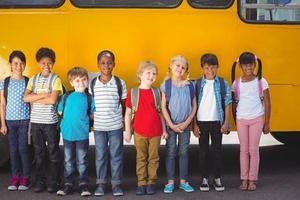 süße Schüler lächeln in der Kamera durch den Schulbus foto