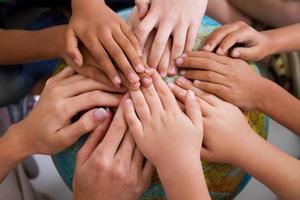 Kinder und Lehrer Hände auf Globus foto