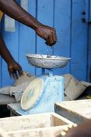 afrikanischer Zimmermann wiegt Nägel auf einer Waage