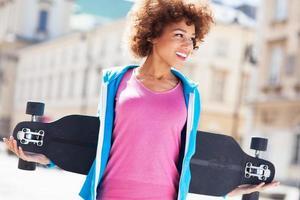 Afroamerikanerfrau, die Longboard trägt