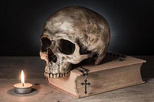 Schädel auf Bibel mit Kerze foto