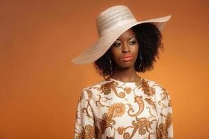 Retro 70er Jahre Mode Afro Frau mit Paisley Kleid und Hut. foto