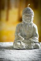 kleine Skulptur von Buddha über weißen Kieselsteinen