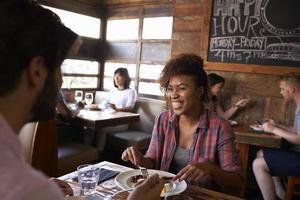 Paar gemischter Rassen, die im belebten Restaurant zu Mittag essen, hautnah