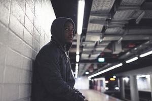 Afroamerikanermann der städtischen Mode mit Kapuzenpulli, der gegen Wand lehnt.