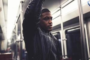 Afro-Mann im urbanen Stil, der in der U-Bahn steht, die Handlauf hält.