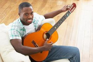 junger Mann, der sich auf dem Sofa entspannt und Akustikgitarre spielt