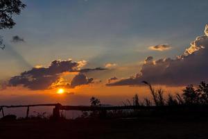 Wolken und Himmel mit Sonnenstrahl am Abend silhouettiert