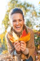 Porträt der glücklichen jungen Frau mit Herbstblättern im Freien