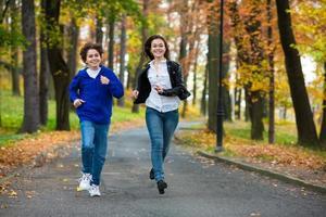 Teenager-Mädchen und Junge laufen im Freien
