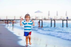 glücklicher kleiner Junge, der am Strand läuft