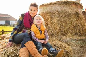 Porträt der glücklichen Frau mit dem niedlichen Kind, das auf Heu sitzt