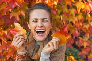 Porträt der glücklichen jungen Frau mit Blättern