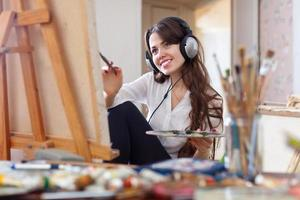 Mädchen in Kopfhörern malt mit Ölfarben auf Leinwand foto