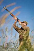 Jäger, der während einer Jagdgesellschaft auf das Spiel zielt foto