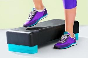 weibliche Füße in violetten Turnschuhen auf Fitnessschritt.