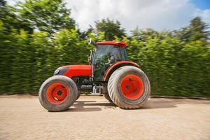Mann mit Traktor in einem Garten, verschwommene Bewegung foto