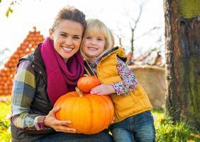 Porträt der glücklichen Mutter und des Kindes, die Kürbis halten