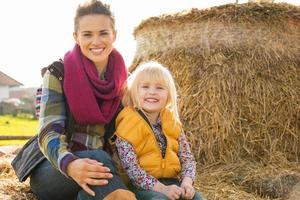 Porträt der glücklichen Mutter und des Kindes, die auf Heuhaufen sitzen