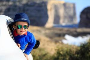 glücklicher kleiner Junge reisen mit dem Auto in den Sommerferien