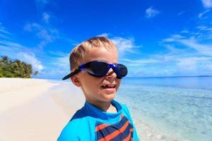 glücklicher Junge in der Schwimmbrille am Strand