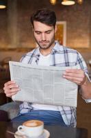 junger Mann, der eine Tasse Kaffee liest Zeitung liest foto