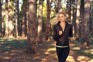 schöne junge Frau, die durch den Park läuft