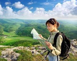 Frau, die Karte beim Wandern betrachtet