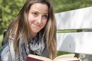 junge Frau, die ein Buch auf einer Parkbank liest