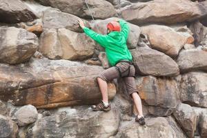 entschlossener Mann, der eine riesige Felswand erklimmt
