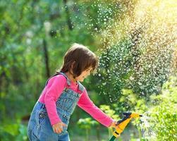 kleines Mädchen, das Garten gießt