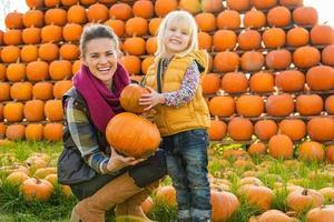 Porträt der glücklichen Mutter und des Kindes, die Kürbisse wählen