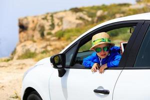 glücklicher kleiner Junge reisen mit dem Auto in den Bergen